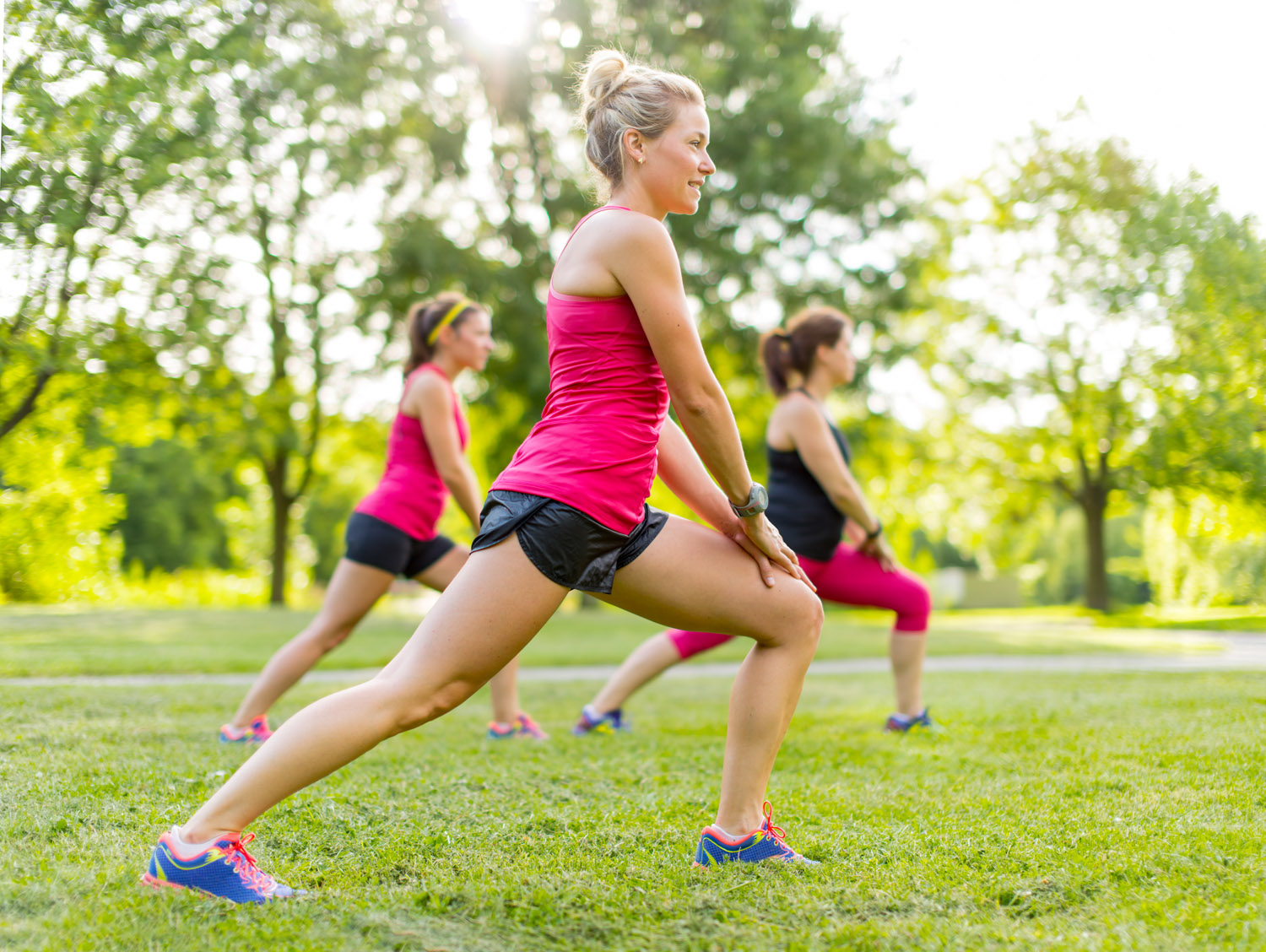 Portrait of three women streching their legs before jogging together